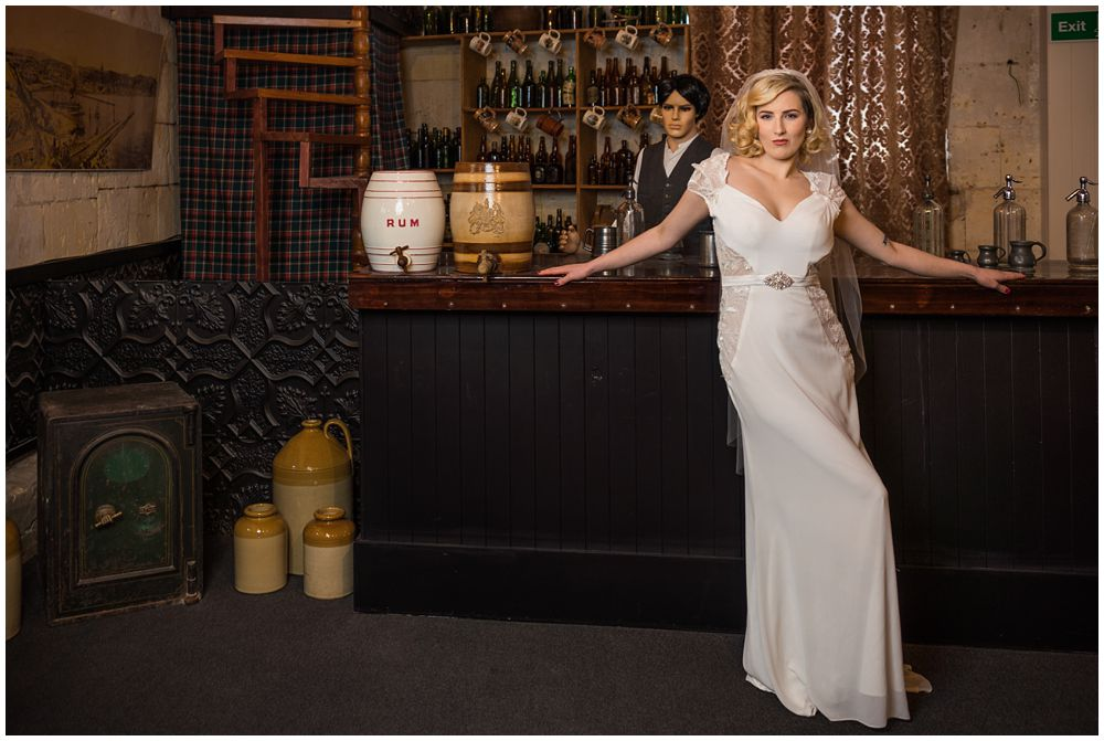 Bride standing with arms on the bar in white wedding dress