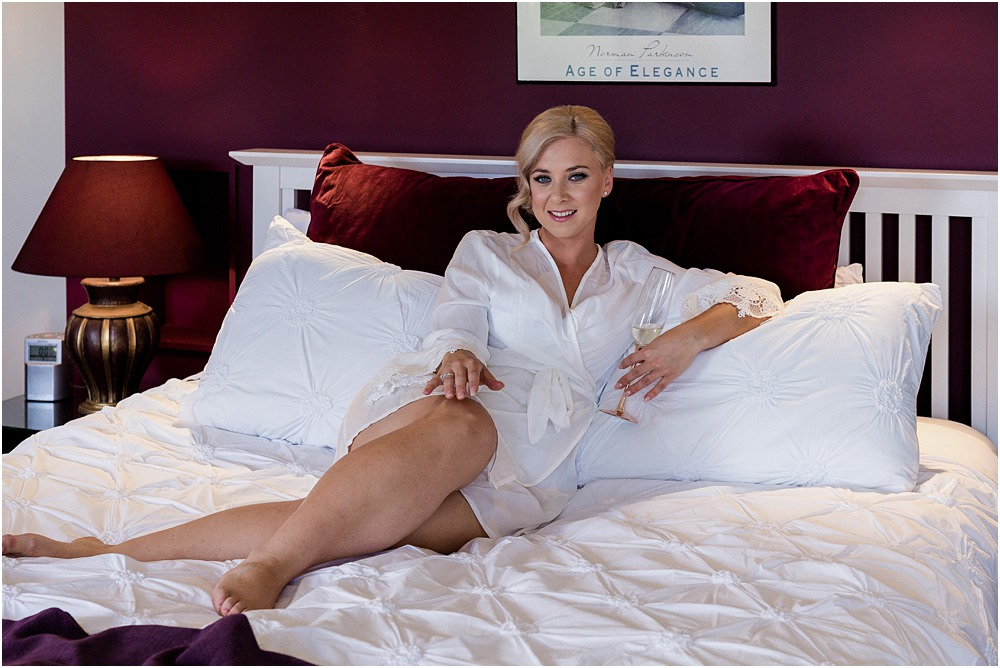 Christchurch Wedding Photographer bride wearing a robe posing for a photo on a bed
