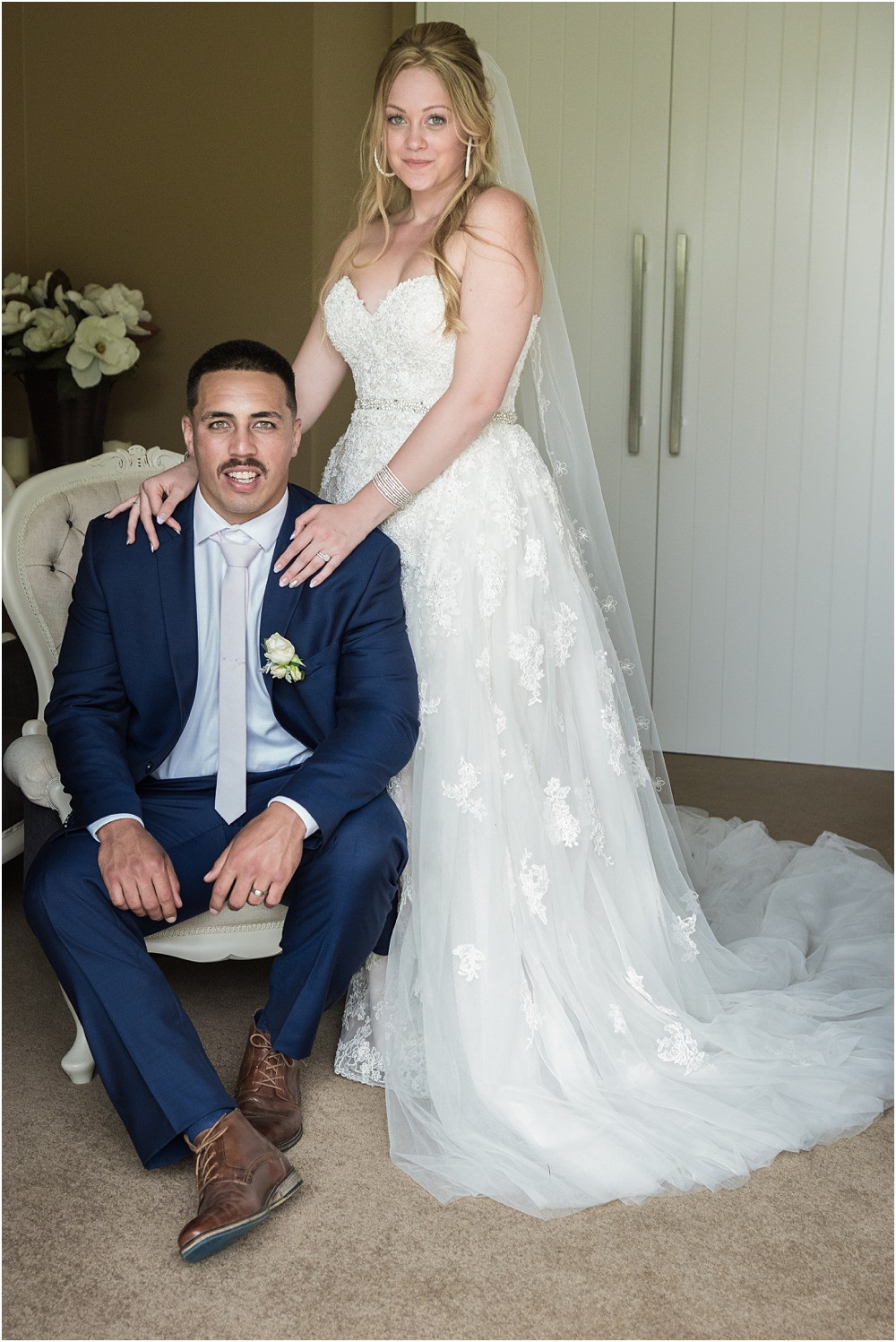 photo of groom sitting on an arm chair with bride's hands on his shoulders in the bridal suite at lacebark wedding venue
