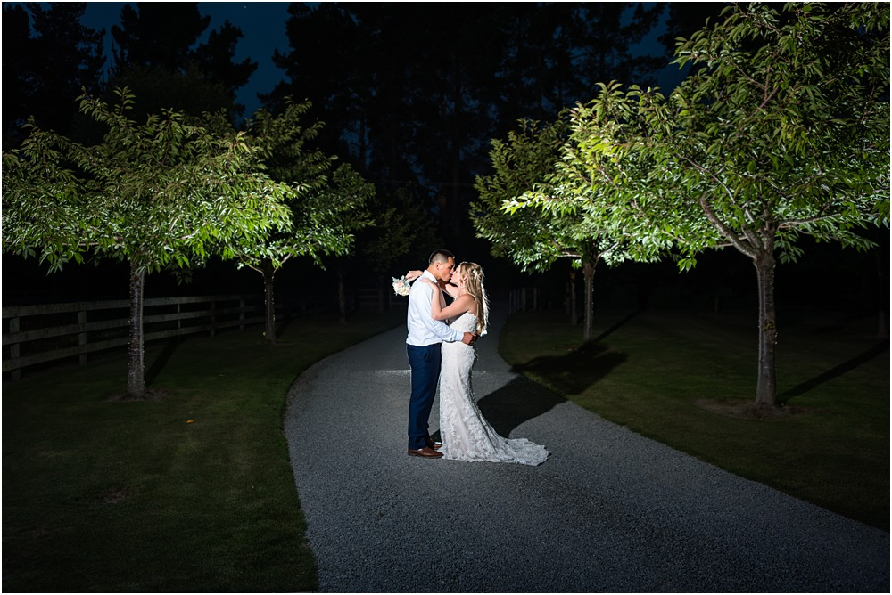 night photos of bride and groom kissing on the driveway at lacebark wedding venue