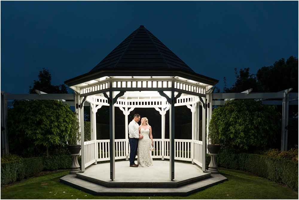 night photos of bride and groom holding hands eye to eye under the gazebo at lacebark wedding venue