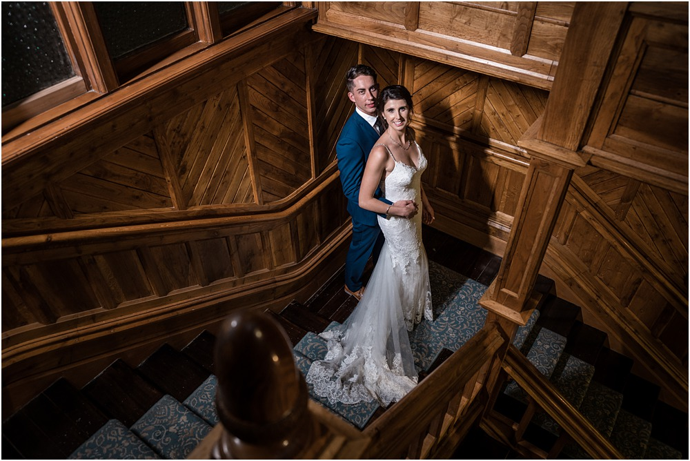 dramatic photo of groom with his hands on the bride's hips standing on the stairs at riccarton house wedding venue