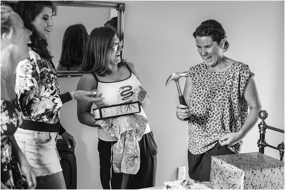 girls laughing at a hammer present one of the bridesmaid received from the bride