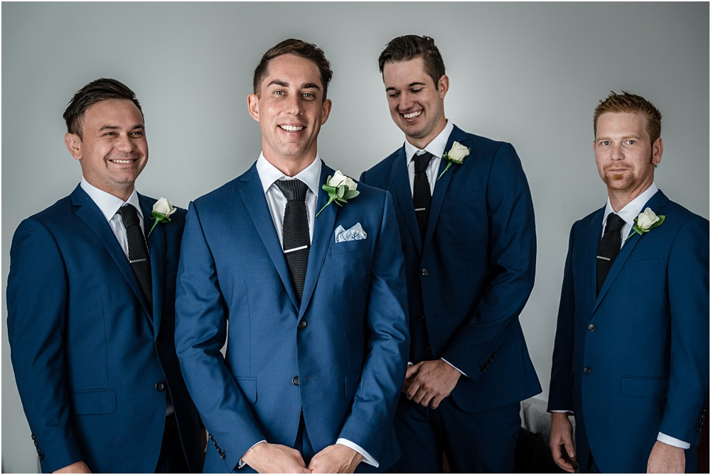 groom and groomsmen standing in a  line dressed in navy blue suits