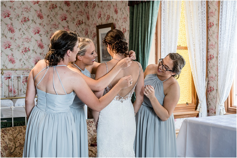 bridesnmaids assisting bride with her dress during wedding preparations at riccarton house