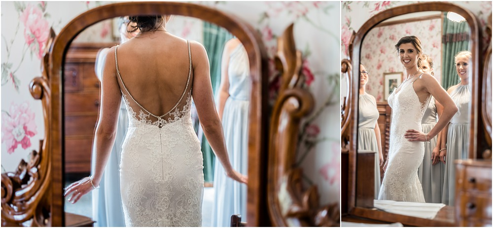 bride's looking at her reflection in the mirror while preparing for wedding at riccarton house
