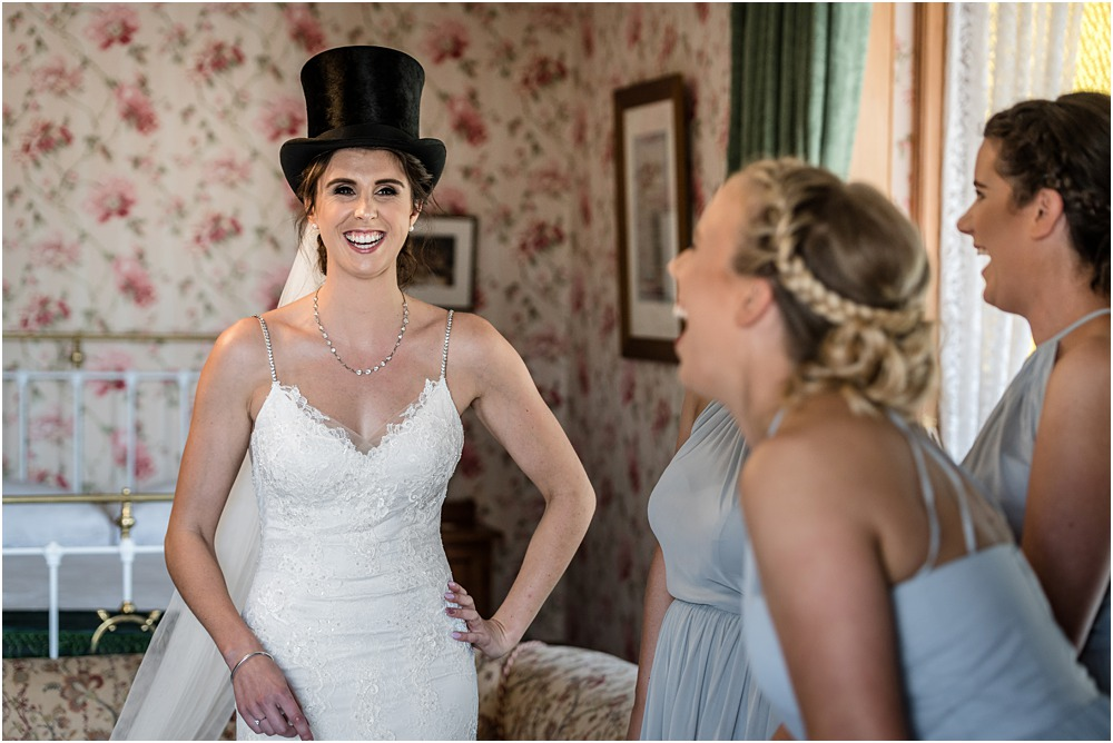 bride playing dress up in a charlie chalpin black hat
