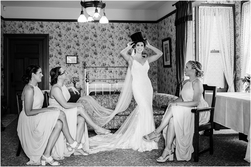 black and white bridesmaids with bride playing dress up in a charlie chalpin black hat