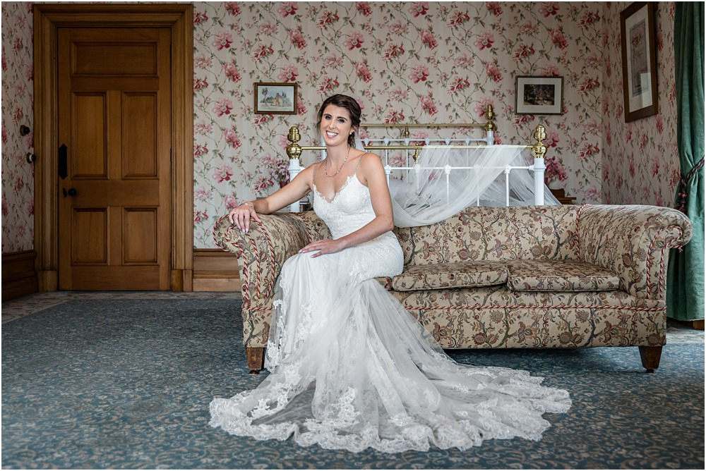 full length portrait of bride sitting on a antique couch at riccarton house wedding venue