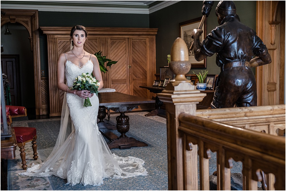 portrait of bride holding her bouquet in the foya at riccarton house wedding venue