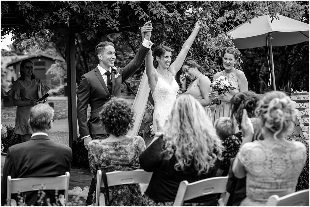 black and white photo of bride and groom lifting thier hands up in the air ccelebrating their marriage