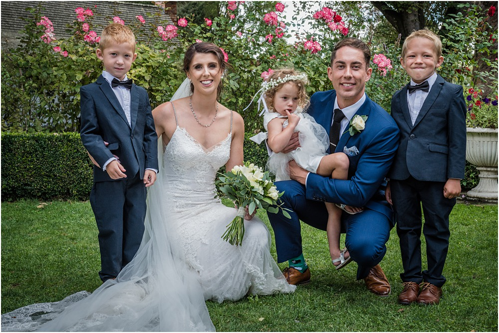 bride and groom pose for a photo with  flowergirl and pageboys