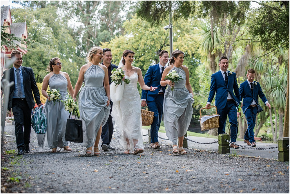 bridal party walking in a line with picnic baskets and flowers in hand