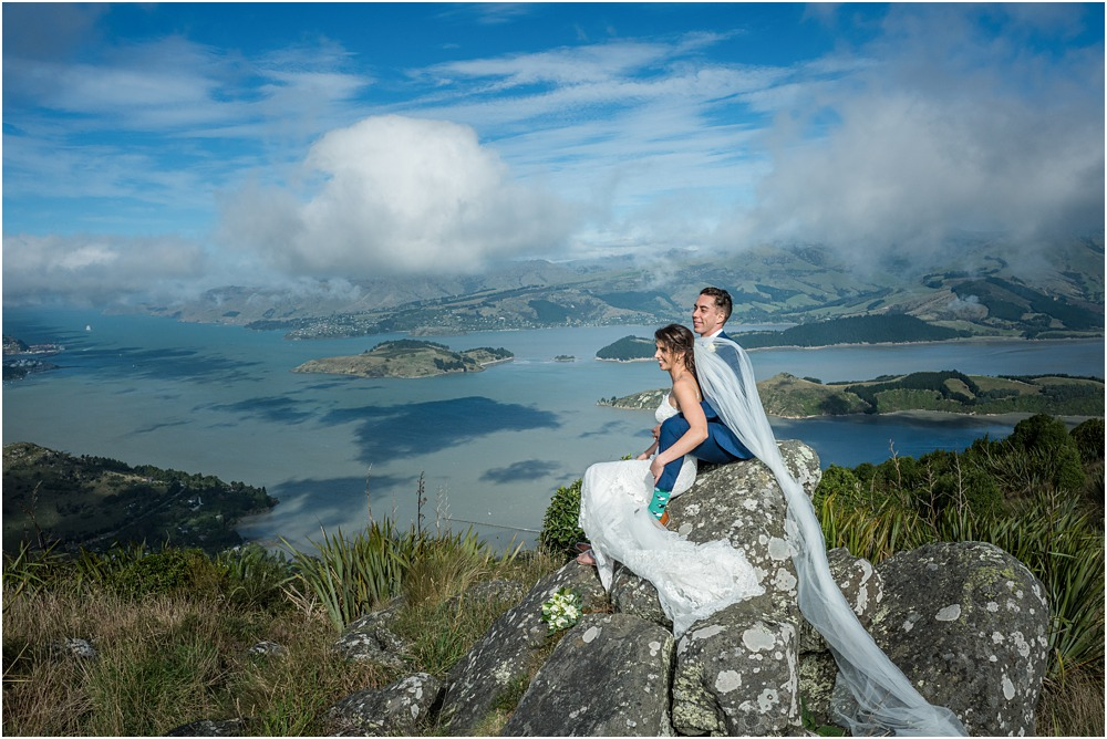 bride and groom sitting on rock at the top of port hills in christchurch