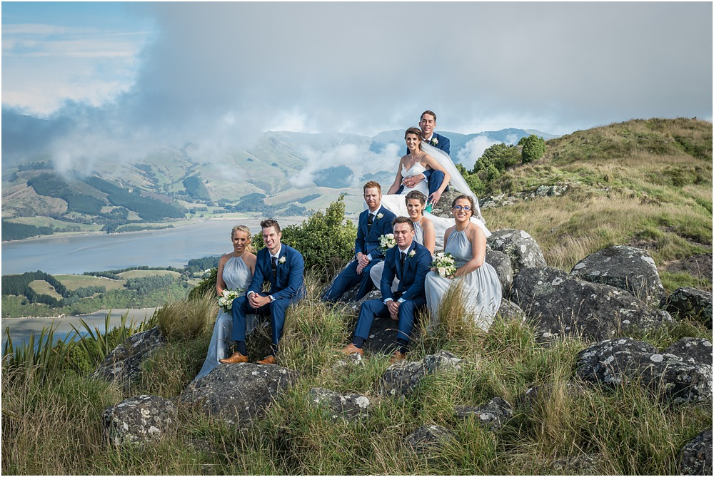 bride and groom and bridal party sitting on rock at the top of port hills in christchurch
