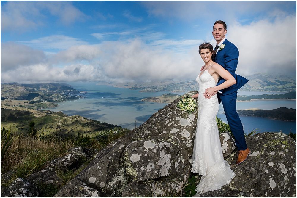 bride and groom standing on rock at the top of port hills in christchurch