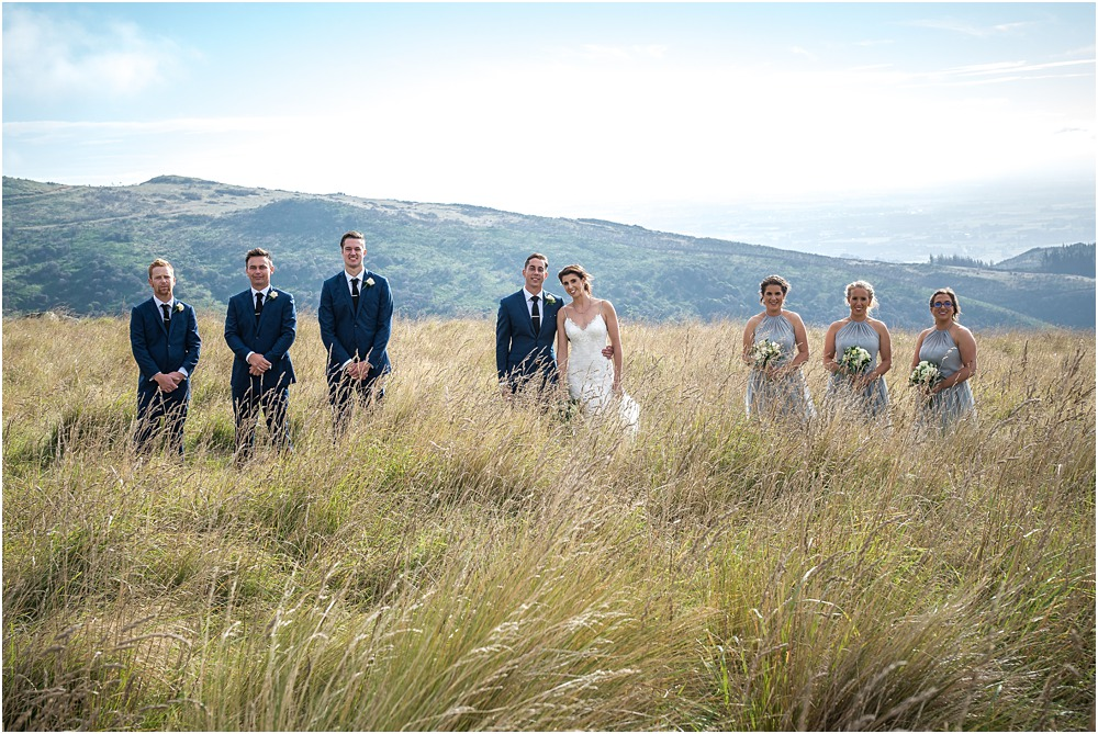 bridal party pose for a photo in long grass