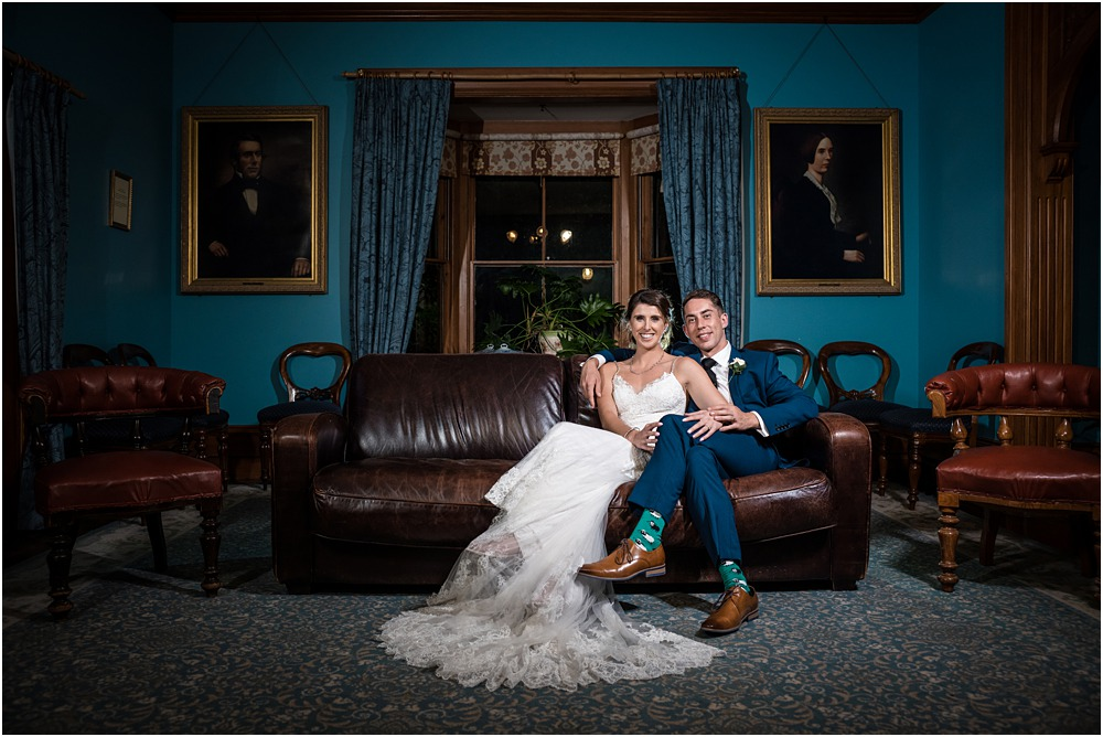 moody photo of bride and groom sitting cuddling on a leather couch at riccarton house wedding venue
