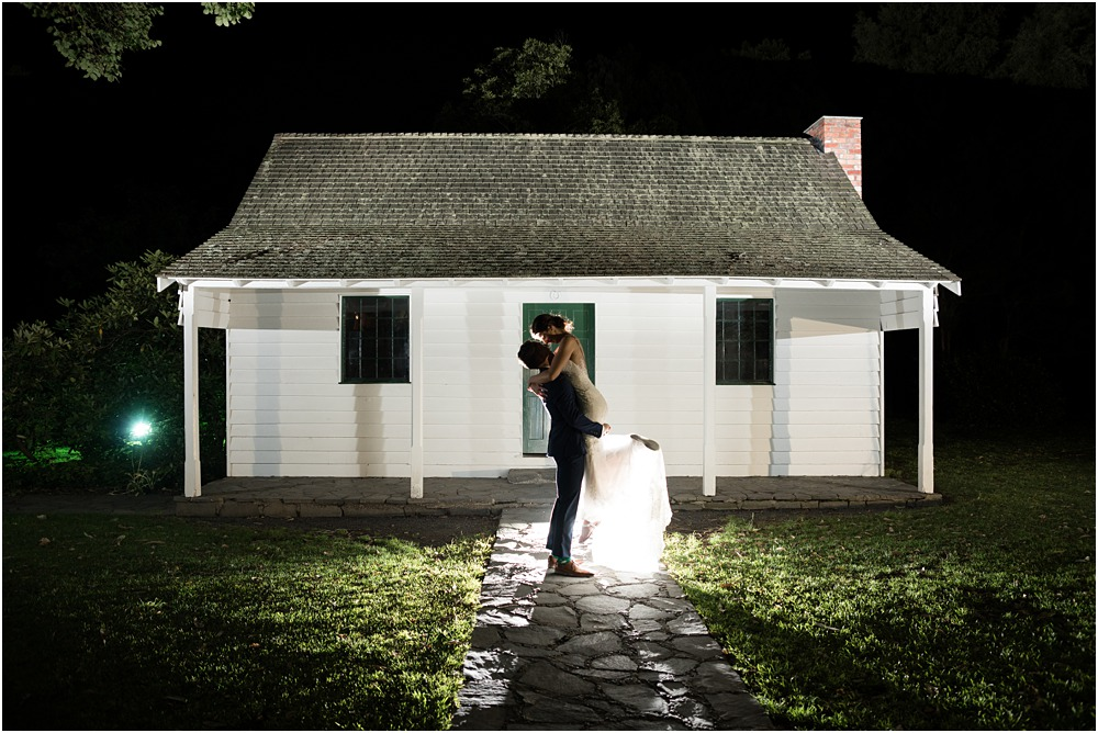night time backlit photo of bride and groom infront of an old white cottage at riccarton house wedding venue