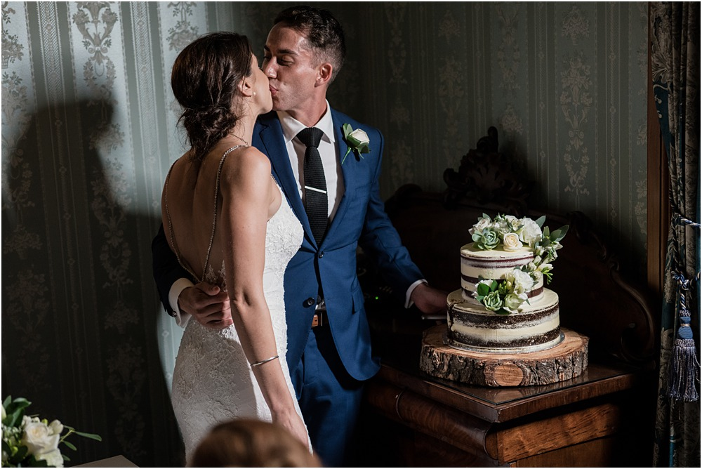 bride and groom kissing after cutting their wedding cake