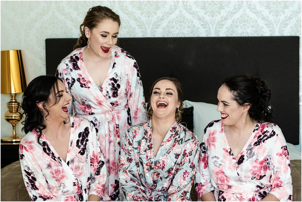 bride and bridesmaids have a laugh sitting on the bed at Braemar Lodge