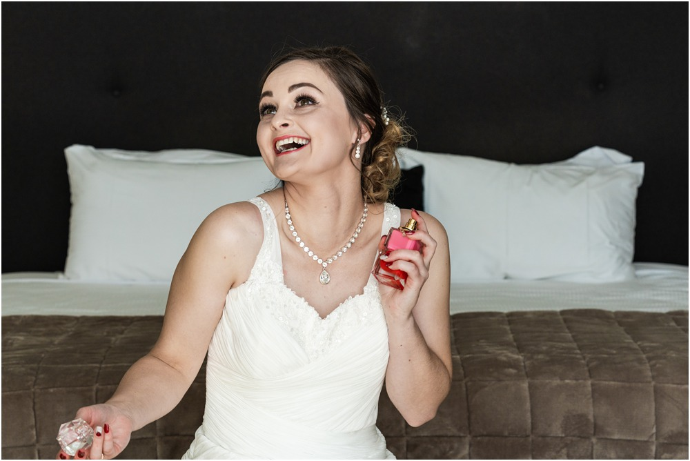 bride playfully applying perfume  on her wedding day