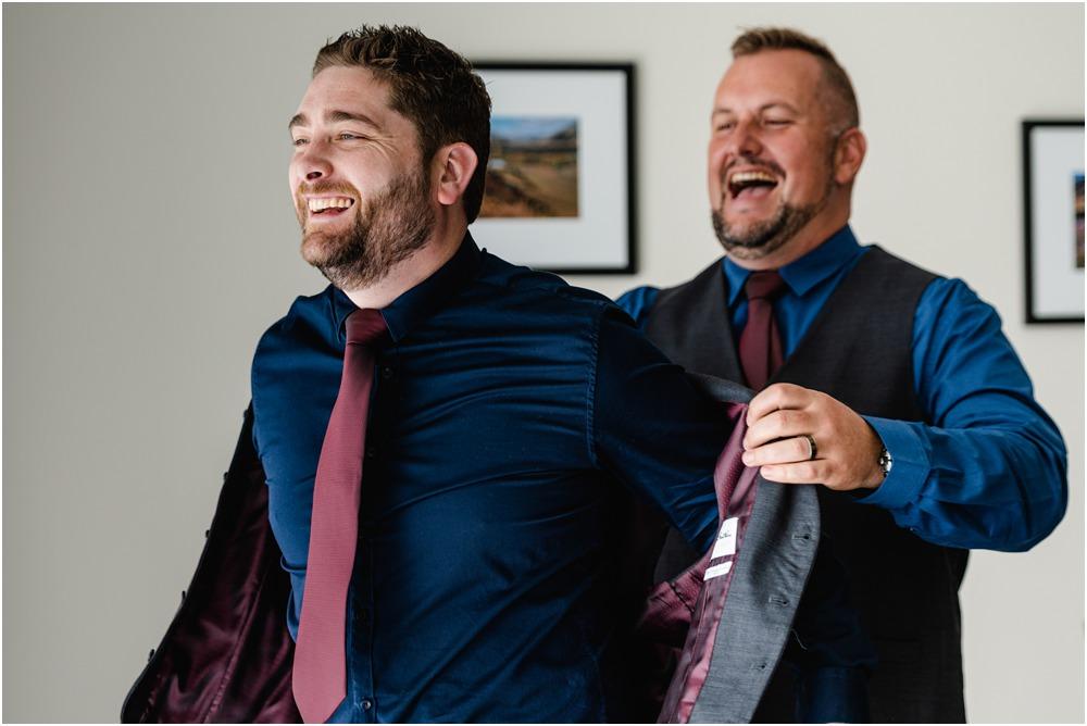 groomsman helping the groom with his wedding jacket at Braemar Lodge