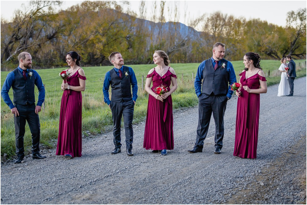 Bridal party standing in the middle of the road with bride and groom in the back ground