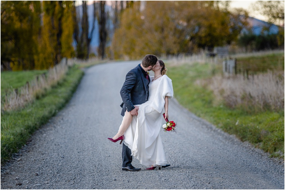 bride and groom kissing in the middle of the road on their wedding day at Braemar Lodge Hanmer Springs