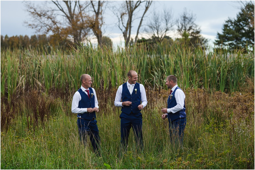 groom and groomsmen standing in long grass