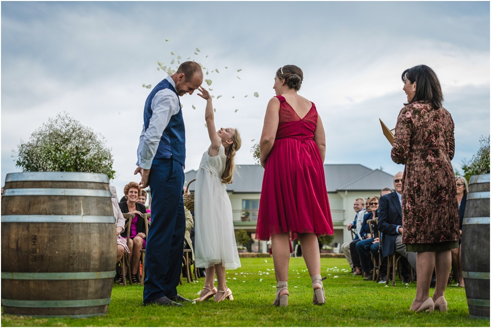 Flower girl throwing petals into the groom's face at Harpers Homestead Wedding