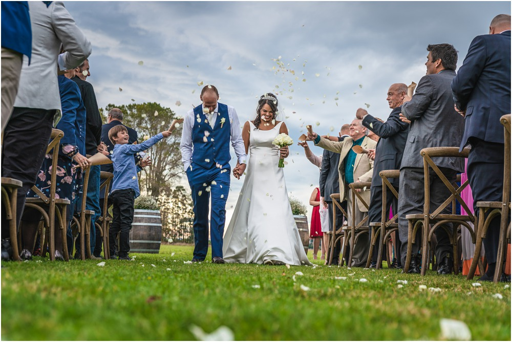 Guests throwing flower petals to the bride and groom at the end of wedding ceremony