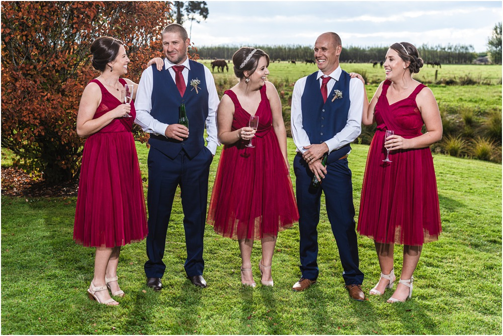 Bridesmaids and groomsmen standing and posing for photo