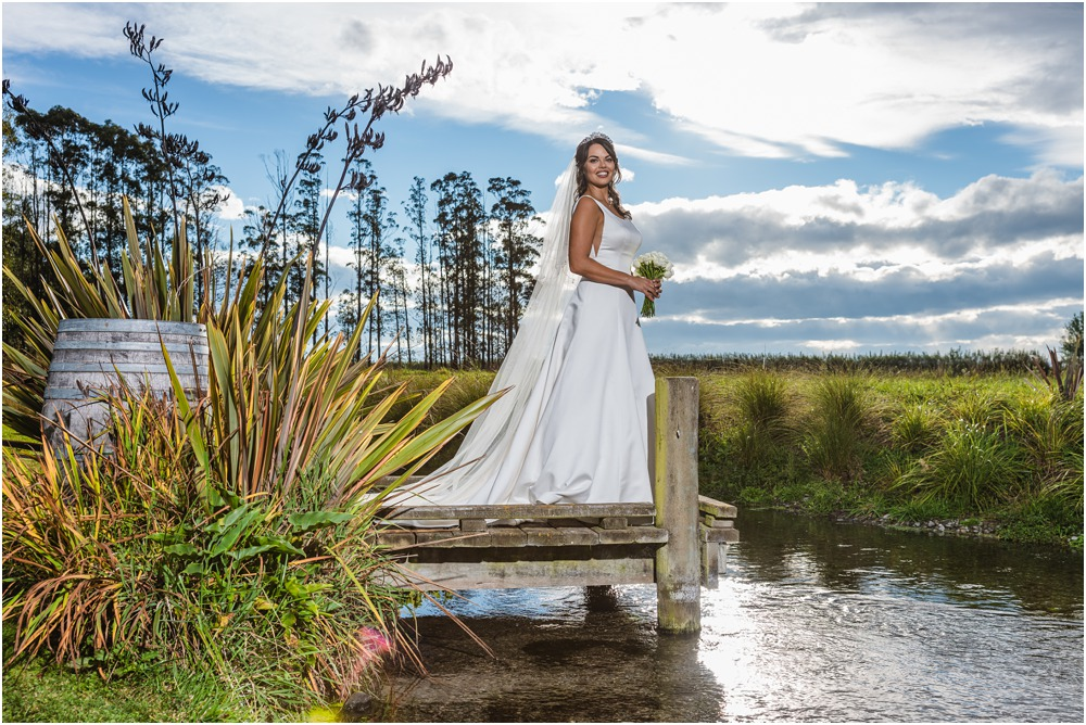 bride stabding on a jetty at Harpers Homestead